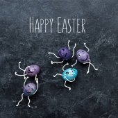 Photo Colorful Easter eggs with drawn faces and happy easter lettering on dark background