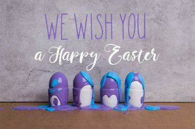Paint covering eggs in cups with we wish you happy easter lettering on grey background
