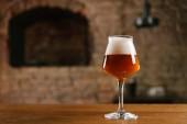 Fotografie Detailní pohled čerstvé točené pivo ve skle na dřevěný stůl v barech