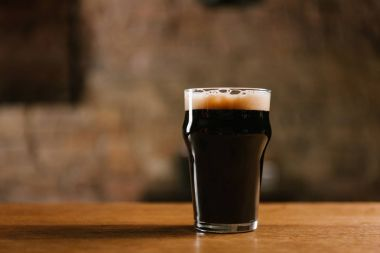 glass of fresh cold dark beer on wooden table in pub