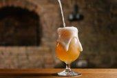 Detailní pohled vylévající čerstvé točené pivo s pěnou do skla v barech
