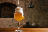 Detailní pohled na nalití piva s pěnou do skla v hospodě