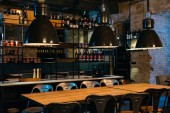 Fotografie wooden tables, lamps and bar counter in modern restaurant