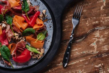 fresh gourmet salad with mussels, vegetables and jamon on plate and fork on wooden table