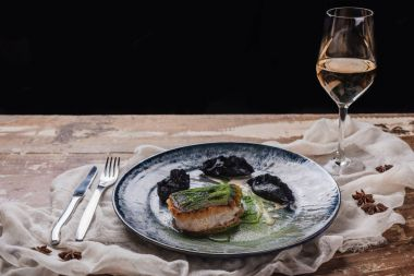 close-up view of gourmet fried zander and glass of wine on wooden table