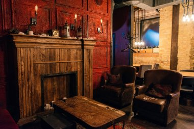 wooden table and empty cozy chairs in atmospheric restaurant