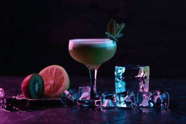 glass of delicious kiwi gin sour cocktail with ice cubes and sliced fruits