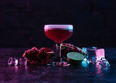 close-up view of glass with delicious conchita cocktail and ingredients on dark surface