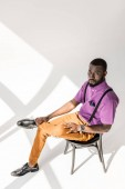 Fotografie high angle view of african american man in stylish clothing sitting on chair on grey background