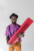 portrait of smiling fashionable african american in hat holding pink wrapping paper rolls in hands on grey backdrop
