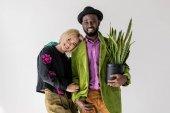Ať se usmívám stylový pár interracial s zelených rostlin květináč suport, izolované Grey