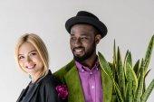Ať se usmívám stylový pár interracial s zelených rostlin v květináč izolované Grey
