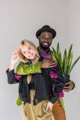 Ritratto di sorridere interrazziale coppie alla moda con la pianta verde in vaso da fiori in posa isolato su grigio
