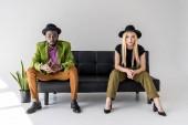 multikulturní módní pár v kloboucích sedí na černé pohovce na šedém pozadí