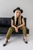 Photo attractive woman in  hat sitting on black sofa on grey backdrop