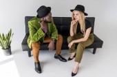 multikulturní módní pár klobouky na sebe dívali na černé pohovce na šedém pozadí