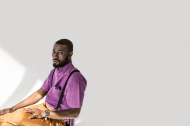 side view of african american man in fashionable clothing sitting on chair on grey backdrop