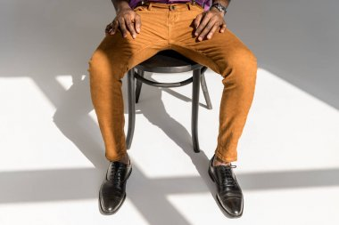cropped shot of african american man in stylish clothing sitting on chair on grey background