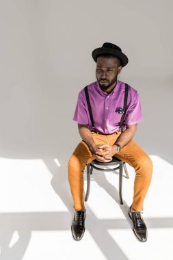 pensive african american man in stylish clothing and hat sitting on chair on grey backdrop
