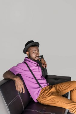 side view of african american man in stylish hat resting on black sofa isolated on grey
