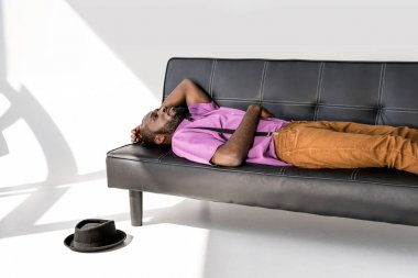 african american fashionable man lying on black sofa with hat on floor on grey backdrop
