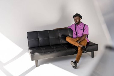 pensive african american stylish man in hat resting on black sofa on grey backdrop