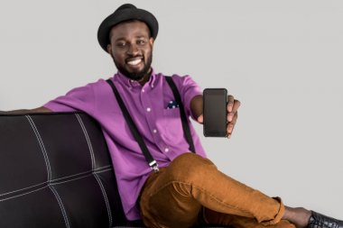 selective focus of smiling african american stylish man showing smartphone with blank screen on black sofa isolated on grey
