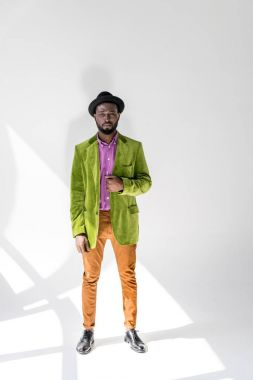 young african american man in fashionable clothing and hat posing on grey backdrop