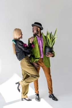 smiling interracial stylish couple with green plant in flowerpot posing on grey backdrop