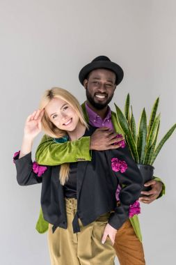 portrait of smiling interracial stylish couple with green plant in flowerpot posing isolated on grey