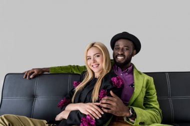 portrait of smiling multicultural fashionable couple resting on black sofa isolated on grey