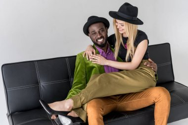 handsome stylish african american man hugging beautiful blonde girlfriend and smiling at camera isolated on grey