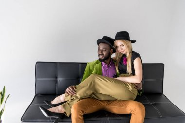 smiling young multiethnic couple in fashionable clothes sitting on sofa and looking away on grey