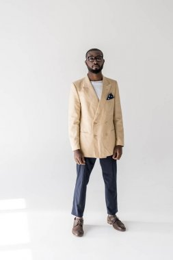 full length view of handsome young african american man in eyeglasses and fashionable clothes looking at camera on grey