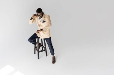 high angle view of fashionable african american man sitting on stool and checking wristwatch isolated on grey