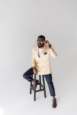 high angle view of handsome young african american man adjusting eyeglasses and sitting on stool isolated on grey