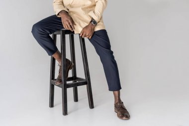 cropped shot of stylish african american man sitting on chair isolated on grey