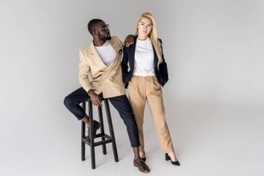 full length view of stylish young multiethnic couple in eyeglasses posing together isolated on grey
