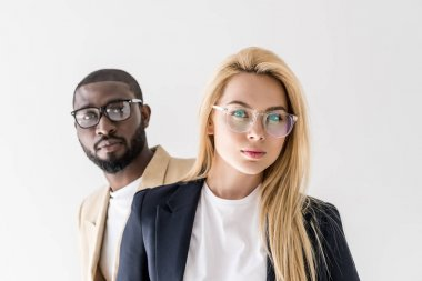 portrait of beautiful stylish young multiethnic couple in spectacles looking at camera isolated on grey