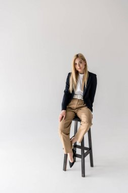 full length view of beautiful stylish blonde girl sitting on chair and looking at camera isolated on grey