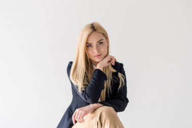 portrait of beautiful stylish blonde girl looking at camera isolated on grey