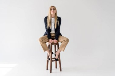 beautiful young blonde woman in stylish clothes sitting on stool and looking at camera isolated on grey