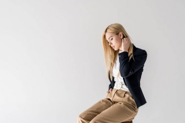 portrait of beautiful young blonde woman in fashionable clothes sitting and looking down isolated on grey