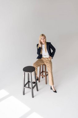 high angle view of beautiful stylish blonde girl sitting on stool and looking at camera on grey