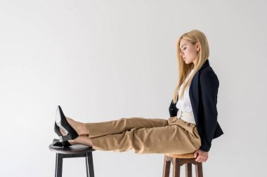 side view of beautiful fashionable blonde girl sitting on stool and looking at legs isolated on grey