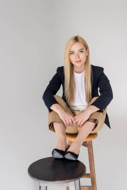 beautiful stylish blonde girl sitting on two chairs and smiling at camera isolated on grey