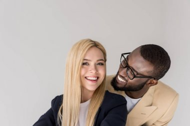 happy young african american man in eyeglasses lookign at beautiful blonde girlfriend isolated on grey