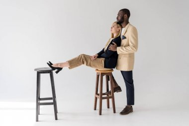 side view of young african american man embracing beautiful stylish girlfriend sitting on chair and looking away on grey