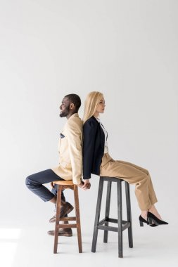 side view of fashionable young multiethnic couple sitting back to back on stools and holding hands on grey