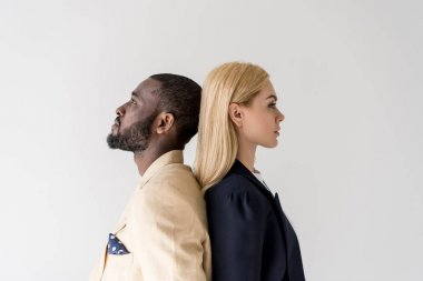 side view of stylish young multiethnic couple standing back to back isolated on grey